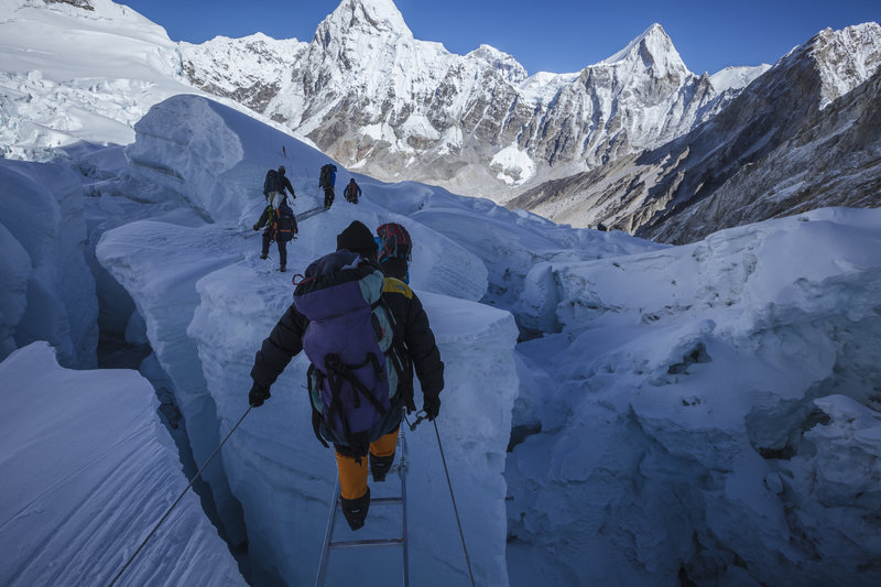 NEPAL - MAY 13: Sherpas step across a bridge of aluminum ladders lashed together above a crevasse in the Khumbu Icefall. Mount Everest, Nepal. (Photo by Andrew Bardon/National Geographic/Getty Images)