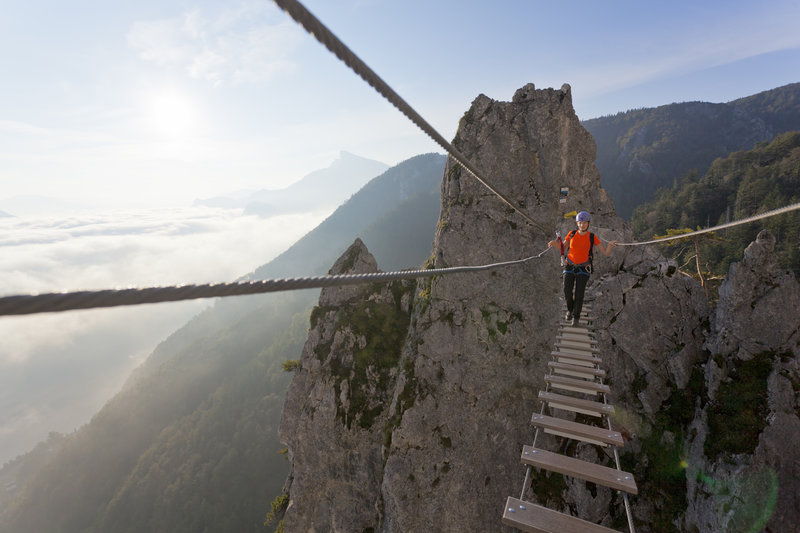 Austria, Mondsee, Woman crossing rope bridge