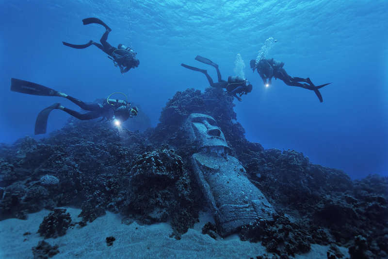 Underwater Moai. Basic Info: Easter Island is the most remote inhabited island in the world. The nearest population center is Chile (2300 miles) and the nearest Polynesian center in the opposite direction is Tahiti (2600 miles). Easter Island, (Rapa Nui, Isla de Pascua) is famous for Moai everywhere along the coast toppled on their AhuÕs and littered abandoned in the center along the Moai roads used to transport them. Polynesians had a knack for colonizing even the most inhospitable oceanic rock. They were adept sailors, explorers, colonizers and their experience taught them the best way to escape war or famine was to sail east, to windward in search of new islands. There is no evidence that a 2nd group reached the island in early history as Heyerdall alledges Ð in fact it points to the opposite. Easter Island had military rule until 1965 and had cashless societies of fishing and farming that have since been broken apart by independence and a dependence on tourism. Rapanui incest laws are strict with everybody tracing roots to 30 or so couples who survived 19th century Peruvian slave raiding and epidemics. Legal romance was at an impasse so mixed marriages now abound on the island.