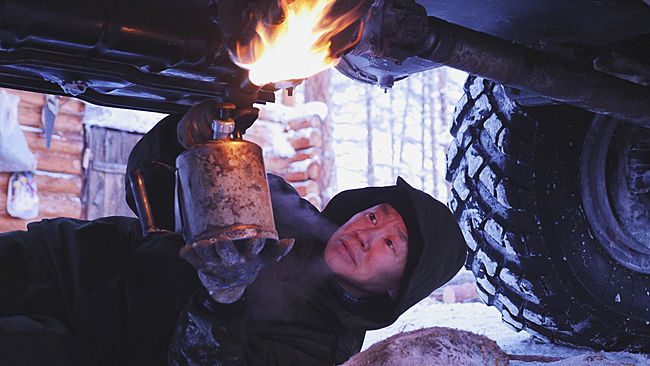A truck driver uses a small flamethrower to thaw the drive shaft of his truck. This picture was taken in the tundra, between Oymyakon and Yakutsk.