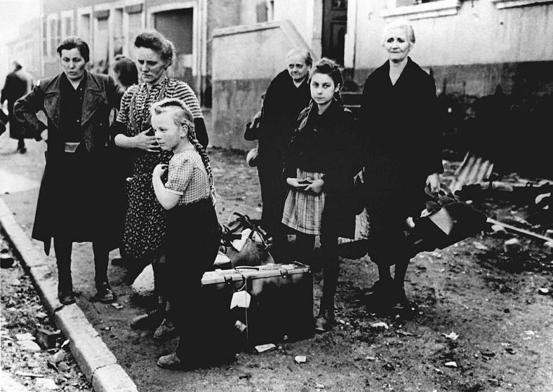 Women and children are standing at the roadside and are waiting for a transport possibility, in 1945. Photo by: dpa/picture-alliance/dpa/AP Images