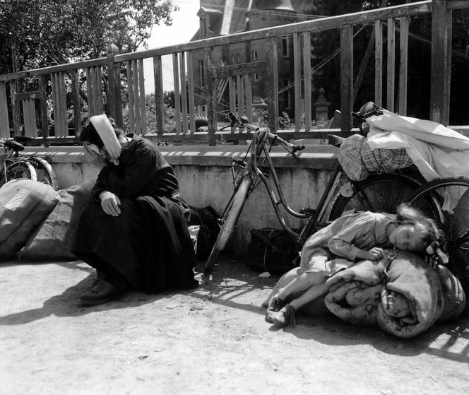 "Refugees fleeing the fighting have brought their bicycles and bundles into a school yard. 10th August 1944. A little girl is lying exhausted on a rolled blanket, while her grandmother is sitting next to her. Her white cap is a ""bachelique"" knitted crochet. Many people from the fighting in Mortaine, just to the south have been seeking refuge in Saint-Pois during August 1944. Mortaine was the final battle for Nornandy. Saint-Pois, Normandy, France. (Photo by Galerie Bilderwelt/Getty Images)"