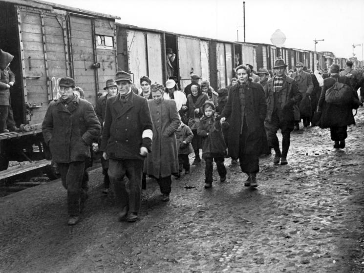 An attendant with white brassard (front, r) accompanies newly arrived refugees, in January 1946, through the refugee camp in Bebra. Photo by: dpa/picture-alliance/dpa/AP Images