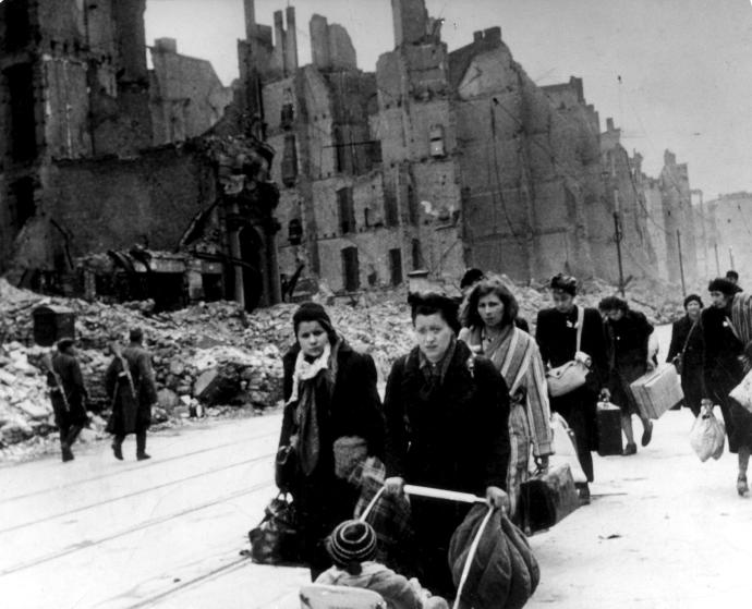 (GERMANY OUT) Stream of refugees and people who have been bombed out of their homes moving through destroyed streets - 1945after end of war; on the left two soviet soldiers patrolling) (Photo by ullstein bild/ullstein bild via Getty Images)